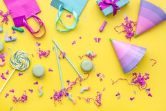 Birthday party accessories. Party hat, sweets, paper bag for gift on yellow background top view copy space pattern.  Stock Image