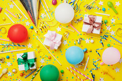 Birthday party background with balloon, gift, confetti, carnival cap, star, candy and streamer. Flat lay style. Colorful card. Stock Photo