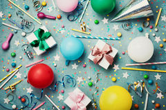 Birthday party background with colorful balloon, gift, confetti, cap, star, candy and streamer. Flat lay style. Festive card.