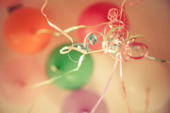 Birthday party background with colourful coiled ribbons and  blurred balloons Stock Images