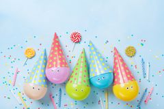Birthday or party background. Funny balloons, candy and confetti on blue table top view. Flat lay. Invitation card. royalty free stock photo