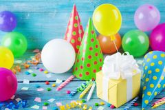 Free Birthday Party Background With Gift Or Present Box, Colorful Balloons, Confetti, Carnival Cap And Streamer. Holiday Supplies Royalty Free Stock Image - 147400196