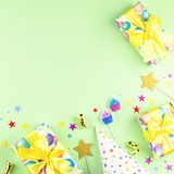 Birthday party background with wrapped gifts, confetti, party hats, decorations, top view stock photo