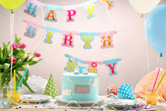 Birthday party with blue cake and balloons.  Stock Images