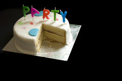 Birthday Party Cake. A birthday cake with candles and missing slice, isolated on black background Stock Image