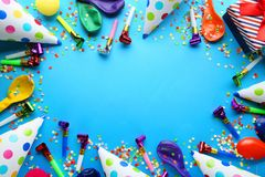 Birthday party caps, blowers and balloons. On blue background royalty free stock photography