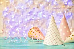 Birthday party caps on table against lights. Birthday party caps on table against blurred lights royalty free stock photos