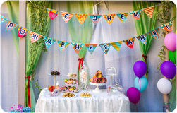 Birthday party of child. Celebration birthday party of child, sweetness, balloons, small flags, evening-party in a garden,treating for guests Stock Photo