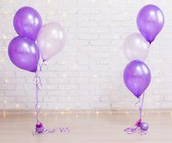 Birthday party concept - brick wall background with lights and a. Birthday party concept - brick wall background with lights and purple air balloons royalty free stock photos