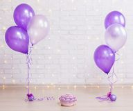 Birthday party concept - cake over brick wall background with li. Ghts and purple air balloons stock photo