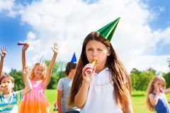 Birthday party. Cute little girl child blow noisemaker on a birthday party wearing cap with friends standing on background Stock Images