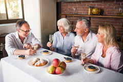 Birthday party of elderly man bin the kitchen. Friends and family gathering around the table to bring birthday greetings to retired men and drink wine together royalty free stock photos
