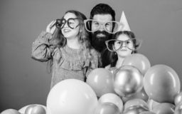 Birthday party. Father with two daughters having fun. Fatherhood concept. Friendly family wear funny party accessories stock images