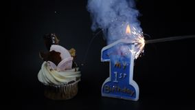 Birthday party feast celebration concept. A cupcake and a burning candle on black. First year anniversary. Burning up a. Sparcler with heavy smoke. Slow motion stock video