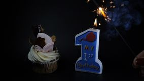 Birthday party feast celebration concept. A cupcake and a burning candle on black. First year anniversary. a sparcler. Burning with heavy smoke. Slow motion stock video