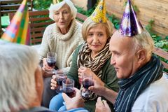 Birthday Party at Full Speed. Group of elderly friends wearing warm clothes holding glasses with red whine in hands and chatting with each other while having royalty free stock image