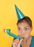 Birthday party funny woman having fun. Funny party woman surprised on yellow background. Beautiful mixed race / asian caucasian model with party hat blowing a stock images
