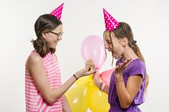 Birthday party. Girls teenagers give a gift. White background, in festive hats with balloons. royalty free stock photography