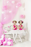 Birthday party happy kids with presents. Girl sisters surprised. By pink gift boxes royalty free stock photos