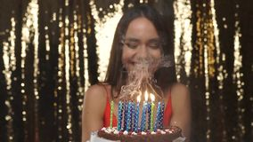 Birthday Party. Happy Woman Blowing Candles On Cake Portrait. Beautiful Smiling Girl Celebrating Holiday On Gold Glitter Background stock video