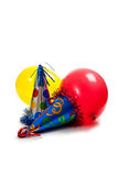 Birthday party hats and balloons on white