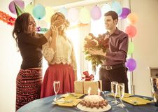 Birthday party at home. Couple and a friend celebrating with a surprise party Stock Photography