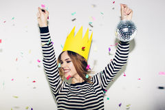 Birthday party, new year carnival. Young smiling woman on white background celebrating brightful event, wears stripped Royalty Free Stock Photography