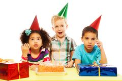 Is birthday party is over already?. Three five years old kids, black and Caucasian, boys and girl with surprised and shocked expression and gesture on the Royalty Free Stock Photo