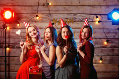 Birthday party teen girlfriends. Young girls in hats and props.  Stock Image