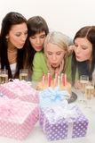 Birthday party - woman blowing candle on cake Royalty Free Stock Image