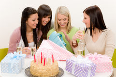 Birthday party - woman unwrap present, celebrating. With champagne and cake Stock Photo