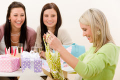 Birthday party - woman unwrap present, celebrating Royalty Free Stock Photo