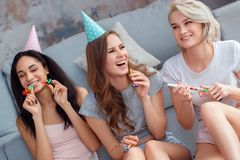 Birthday Party. Young women in caps at home together sitting on floor with party horns laughing cheerful close-up stock images