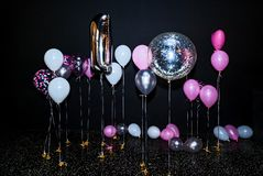 Birthday photo zone. Festive photo area with decorations from a large inflatable number one with white, pink and gray balloons, free space. Black background stock photography