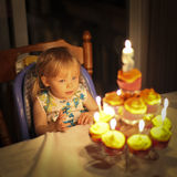 Birthday. Picture of a young girl celebrating her second birthday. She is  seated in front of her birthday cake, amazed and waiting to blow the candles out Royalty Free Stock Image