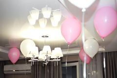 Birthday pink balloons under the ceiling at home stock images