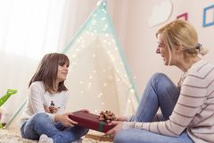 Birthday present. Young mother giving a birthday present to her daughter. Focus on the daughter royalty free stock photos