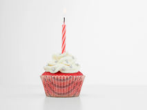 Birthday red muffin candle. Red muffin with cream  white and candy silve one red spiral burning candle on white background Royalty Free Stock Image