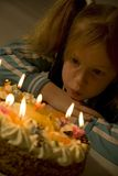 Birthday of a small girl. A young girl blowing out her birthday-candles royalty free stock images