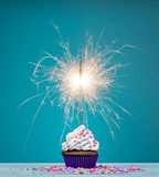 Birthday Sparkler Cupcake. Birthday cupcake with sparkler and sprinkles over a blue background Royalty Free Stock Photography