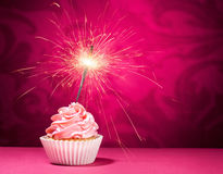 Birthday Sparkler Cupcake. Cupcake with sprinkles and a sparkler over a pink background stock image