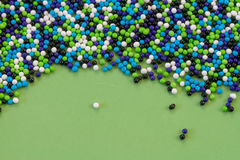 Birthday Sprinkles. Light blue, royal blue, green, and white cake sprinkles against a green background Royalty Free Stock Photo