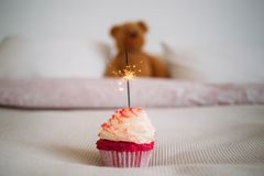 Birthday surprise cupcake with sparkle on bed. Vintage hipster analog effect photo of happy birthday pink cupcake with whipped cream and sparkle candle burning Royalty Free Stock Photo