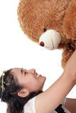 Birthday surprise teddy bear. Beautiful Asian girl smiling at a big teddy bear she holds up above her, isolated on white background Stock Photos