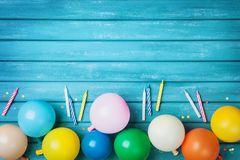Birthday table with colorful balloons, confetti and candles top view. Party background. Festive greeting card. stock photos