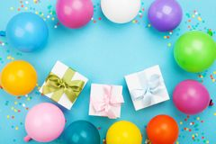 Birthday table with colorful balloons, gift or present box and confetti top view. Flat lay composition. Birthday table with colorful balloons, gift or present Stock Photography
