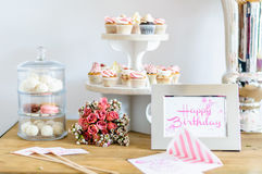 Birthday table. Happy birthday greeting card with color fitting bouquet of flowers and cupcakes Royalty Free Stock Photo