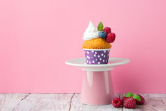 Birthday vanilla cupcakes with fresh raspberries. Delicious birthday vanilla cupcake with fresh raspberries, blueberries and cream on a pink background Stock Images