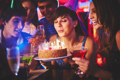Birthday wish. Happy girl blowing on candles on birthday cake with her friends near by royalty free stock image