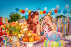Birthday. Young mother comforts crying baby girl in birthday hat, which throwing a tantrum Royalty Free Stock Images
